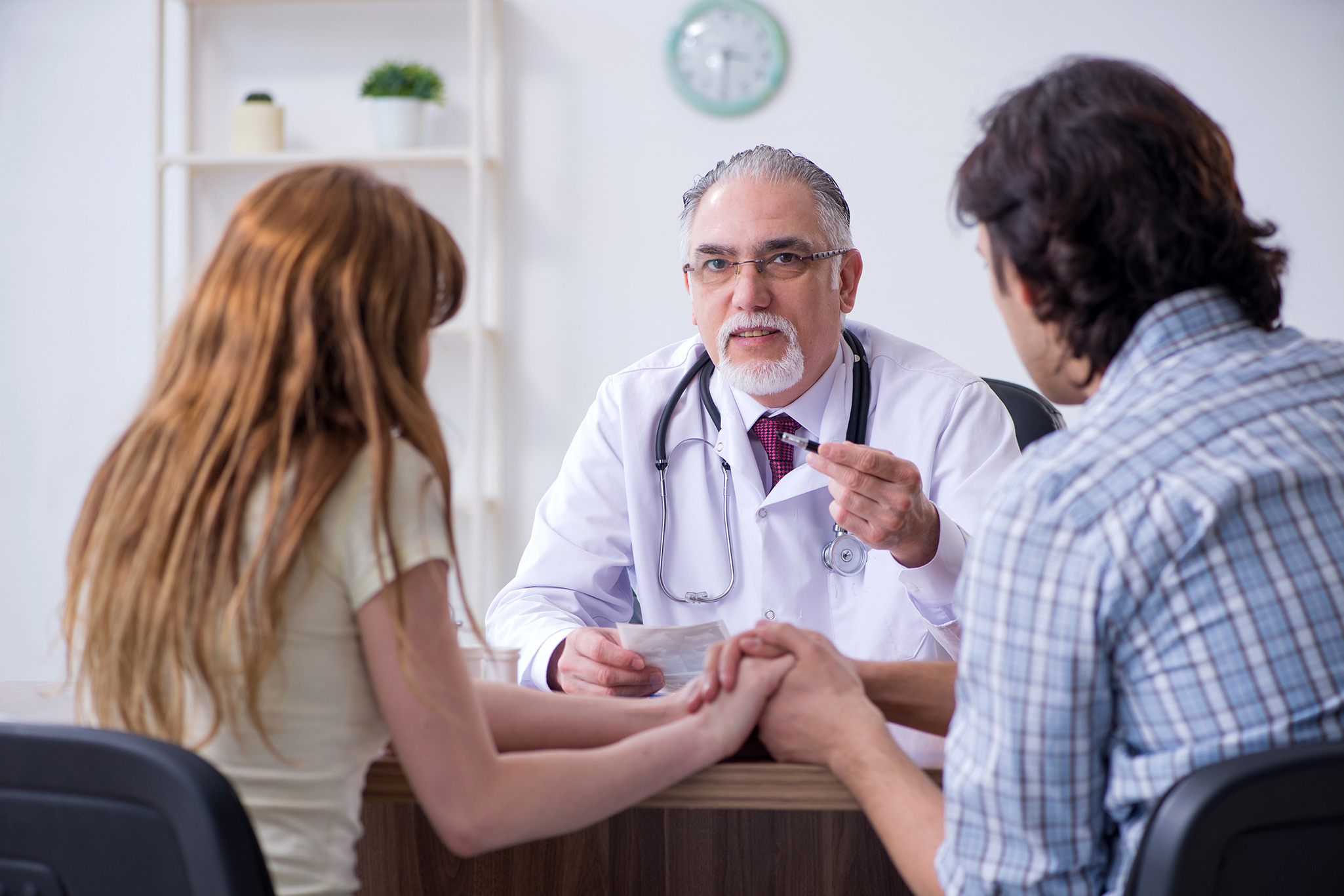 A woman and a man holding hands while talking to a doctor